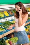 Mercearia - mulher que prende o telefone móvel Imagem de Stock Royalty Free