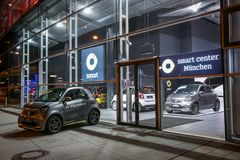 Mercedes Benz dealership in Munich. MUNICH, GERMANY - DECEMBER 11, 2017 : A Smart car exhibited at Smart center in front of the Mercedes Benz dealership building Royalty Free Stock Photography