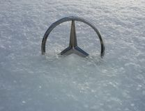 Mercedes-Benz mascot hood ornament half-buried in fluffy show in Rostov-on-Don, Russia stock photography