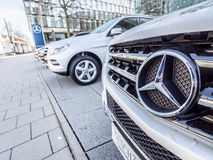 Mercedes-Benz sign. Mercedes-Benz cars at a dealership - focus is on the right side of the prominent Mercedes-Benz sign, copy space to the left royalty free stock image