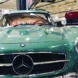 1955 Mercedes Benz 300 SL. Two-door Gullwing Coupe with green body with chrome trim. Black tires with green and chrome rims and hub caps. Chrome bumper with a Stock Photo