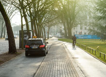 Mercedes-Benz taxi and cyclist on special lane. STRASBOURG, FRANCE- FEB 2, 2017: Mercedes-Benz taxi van exiting special taxi parking near the European PArliament Royalty Free Stock Photography