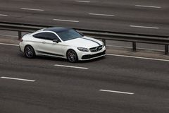 Mercedes coupe white rides on the road. Against a background of blurred trees stock image