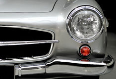 Mercedes front body detail. Mercedes 300 SL 1957 front body detail showing headlight, orange winker, bumper, bonnet, grill, and silver coachwork Royalty Free Stock Images