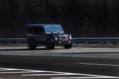 Mercedes G55 monta en el camino Contra un fondo de árboles borrosos imagenes de archivo