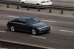 Mercedes S class black rides on the road. Against a background of blurred trees stock image