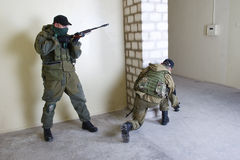 Mercenary with AK rifle. Throw a grenade inside the building Stock Photo