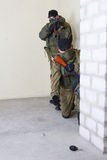 Mercenary with AK rifle. Throw a grenade inside the building Stock Photos