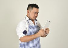 Merchant Asian fat man in white and blue apron is use technology read  data news from connection internet in tablet. With white background Royalty Free Stock Image