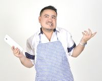 Merchant Asian man in white and blue apron is feeling regret or boring when get bad news from connection internet in tablet. Merchant Asian man in white and blue Royalty Free Stock Images
