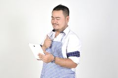 Merchant Asian man in white and blue apron is feeling surprised or excited when get good news from connection internet in tablet. With white background Royalty Free Stock Images