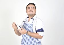 Merchant Asian man in white and blue apron is feeling surprised or excited when get good news from connection internet in tablet. With white background Stock Images