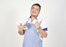 Merchant Asian man in white and blue apron is feeling surprised or excited when get good news from connection internet in tablet. With white background Stock Photography