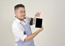 Merchant Asian man in white and blue apron is feeling surprised or excited when get good news from connection internet in tablet. With white background Stock Image