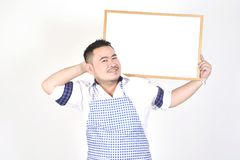 Merchant Asian man in white and blue apron to holding blank white broad for put some text or wording for present advertising. With white background Stock Photo