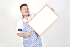 Merchant Asian man in white and blue apron to holding blank white broad for put some text or wording for present advertising. With white background Royalty Free Stock Photo