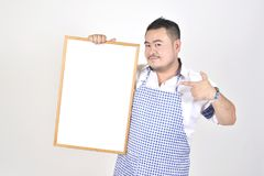 Merchant Asian man in white and blue apron to holding blank white broad for put some text or wording for present advertising. With white background Stock Images