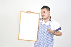Merchant Asian man in white and blue apron to holding blank white broad for put some text or wording for present advertising. With white background Royalty Free Stock Image