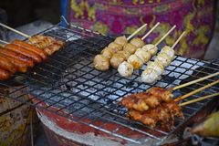 Merchant are grilled meet ball and meet stick on street road.  Royalty Free Stock Images
