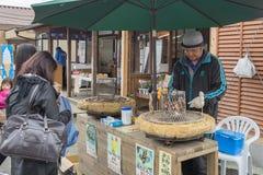 Merchant selling Tanuki Dango on stove Royalty Free Stock Photos