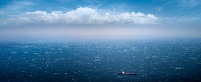 Merchant ship and bad weather. Transport ship sailing on the sea on a background of beautiful clouds Royalty Free Stock Photography