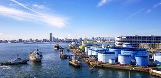 Port activity in Tokyo , Japan. with Mount Fuji in the background. Merchant ship is going to dock into the port near Tokyo , Japan. The port also has oil tanks royalty free stock images