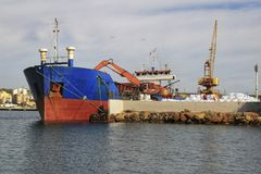 Merchant ship unloading at the dock. In Santa Pola Royalty Free Stock Photo