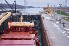 Merchant ship vessel with two cranes passing locks in the Great Lakes, Canada in winter time. New locks are equipped with suction pads stock image