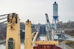 Merchant ship vessel with two cranes passing locks in the Great Lakes, Canada in winter time. New locks are equipped with suction pads royalty free stock photos