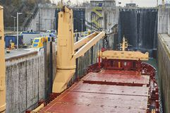 Merchant ship vessel with two cranes passing locks in the Great Lakes, Canada in winter time. New locks are equipped with suction pads royalty free stock image