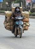 Merchant transports many boxes on the back of motorcycle. Stock Photos