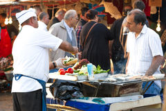 Merchants. A trader serves food fast food market stock photo