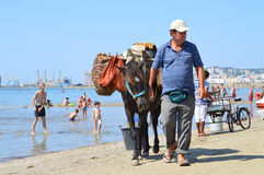 Merchants on the beach of Durres. DURRES, ALBANIA – August 30, 2015: Man with donkey sales figs on the beach. Albania has two faces - backwardness and poverty Stock Photos