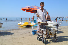 Merchants on the beach of Durres. DURRES, ALBANIA – August 30, 2015: Merchant on the beach sales grilled in a wheelbarrow sweet corn. Albania has two faces Stock Photos