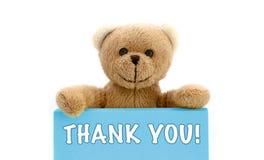 MERCI ! écrit sur la carte bleue avec l'ours de nounours brun tenant avec les deux mains la note avec le message photos stock