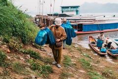 Merci commoventi della gente alla terra in barca nel fiume a Luang Prabang, Laos Fotografia Stock