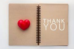 Merci concept avec le carnet ouvert de blanc et le coeur rouge jpg Photos libres de droits