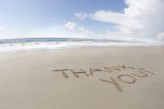 Merci écrit sur une plage Photographie stock