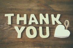 Merci des lettres au-dessus de table en bois vintage filtré et modifié la tonalité Image stock