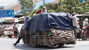 Merci di trasporto dei lavoratori in motocicletta e carretto Fotografia Stock