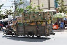 Merci di trasporto dei lavoratori in motocicletta e carretto Immagini Stock