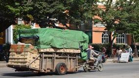 Merci di trasporto dei lavoratori in motocicletta e carretto Immagini Stock Libere da Diritti