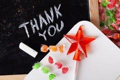 Merci espacer écrit sur un tableau noir avec la craie, caramel, sucrerie, étoile, baguette magique, jour de valentines, signe de  image stock