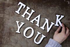 Merci exprimer des lettres en bois blanches sur la table et les mains images stock