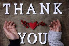 Merci exprimer des lettres en bois blanches sur la table et les mains photographie stock