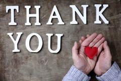 Merci exprimer des lettres en bois blanches sur la table et les mains photos stock