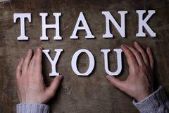 Merci exprimer des lettres en bois blanches sur la table et les mains Image stock
