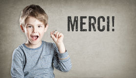 Merci, French thanks, Boy on grunge background writing Royalty Free Stock Image