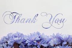 Merci - les fleurs et le texte d'isolement sur le blanc Photo libre de droits