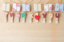 Merci mot de corde à linge avec des boîte-cadeau sur la table en bois Photo stock